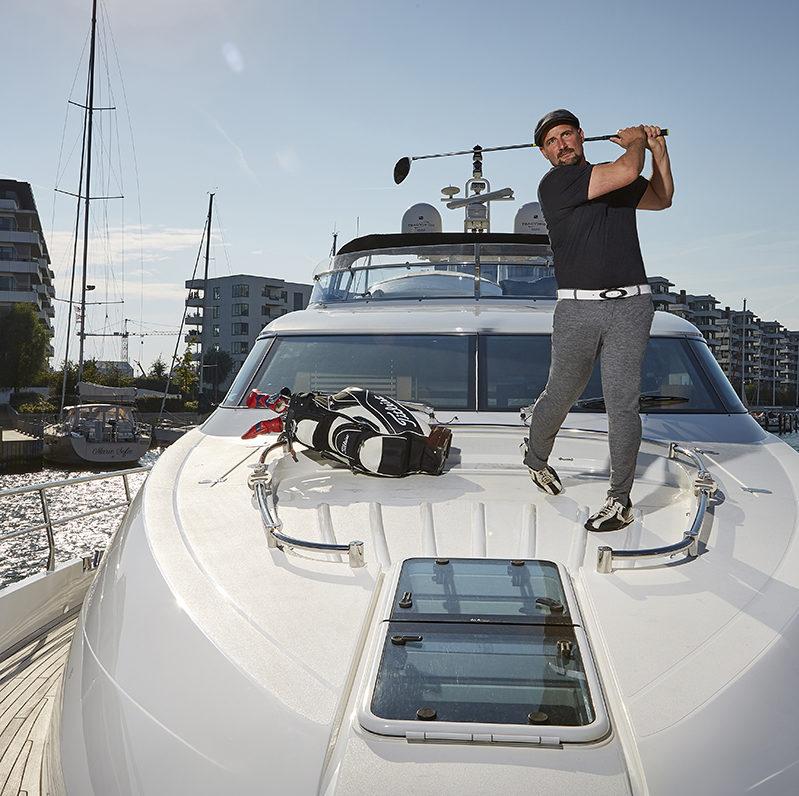 En mand står på en stor båd og spiller golf