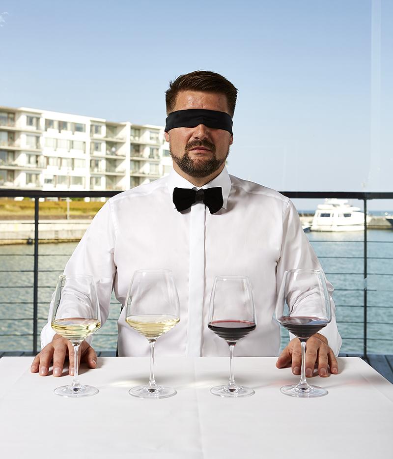 En mand sidder til vinsmagning og blindsmagning med havnen i baggrunden