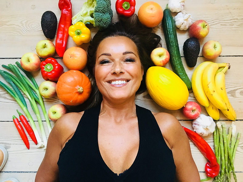 Martina S. Banach ligger på gulvet omgivet af frugt og grønt