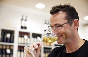 Vinhandler drikker af et glas vini sin butik